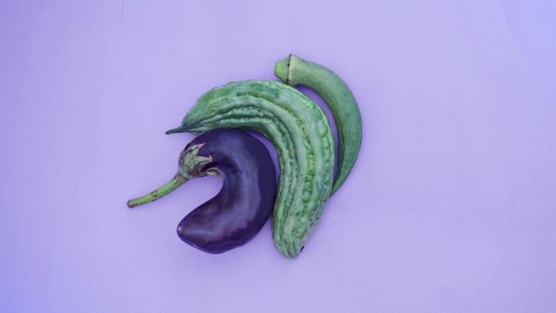O objetivo da Omens é explicar os sintomas, causas e soluções para quem tem um pênis torto (doença de Peyronie). A imagem mostra três legumes tortos num fundo roxo que evocam um pênis torto.