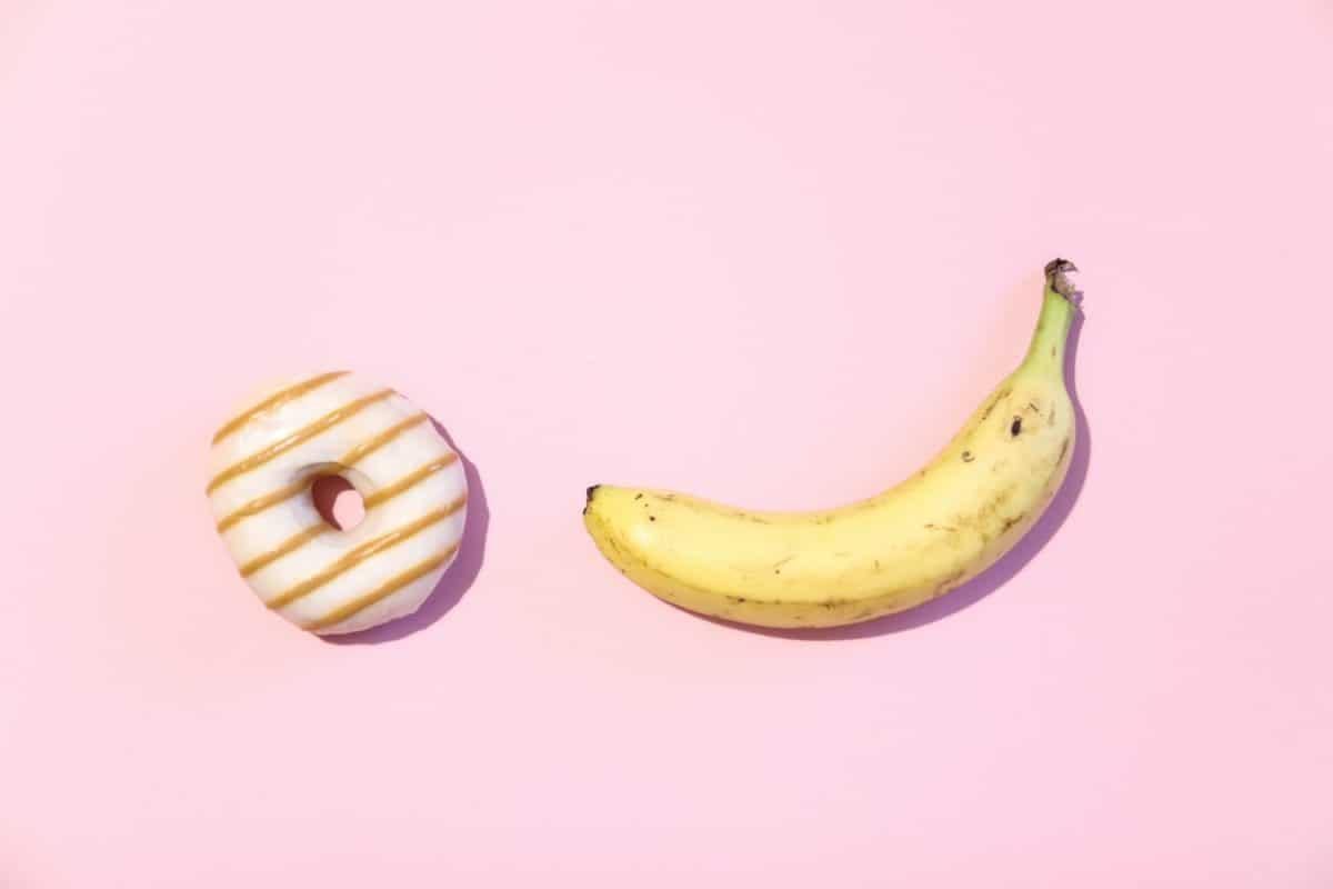 O objetivo da Omens é dar dicas sobre como usar um anel peniano . A imagem mostra uma banana e um donut em um fundo rosa.