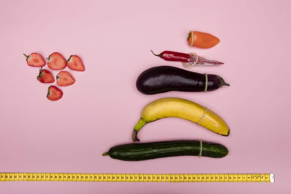O objetivo da Omens é dar dicas sobre como saber o tamanho da camisinha . A imagem mostra um pimentão laranja, uma pimenta vermelha, uma berinjela, uma banana e um pepino de vários tamanhos embrulhados num preservativo em um fundo rosa.