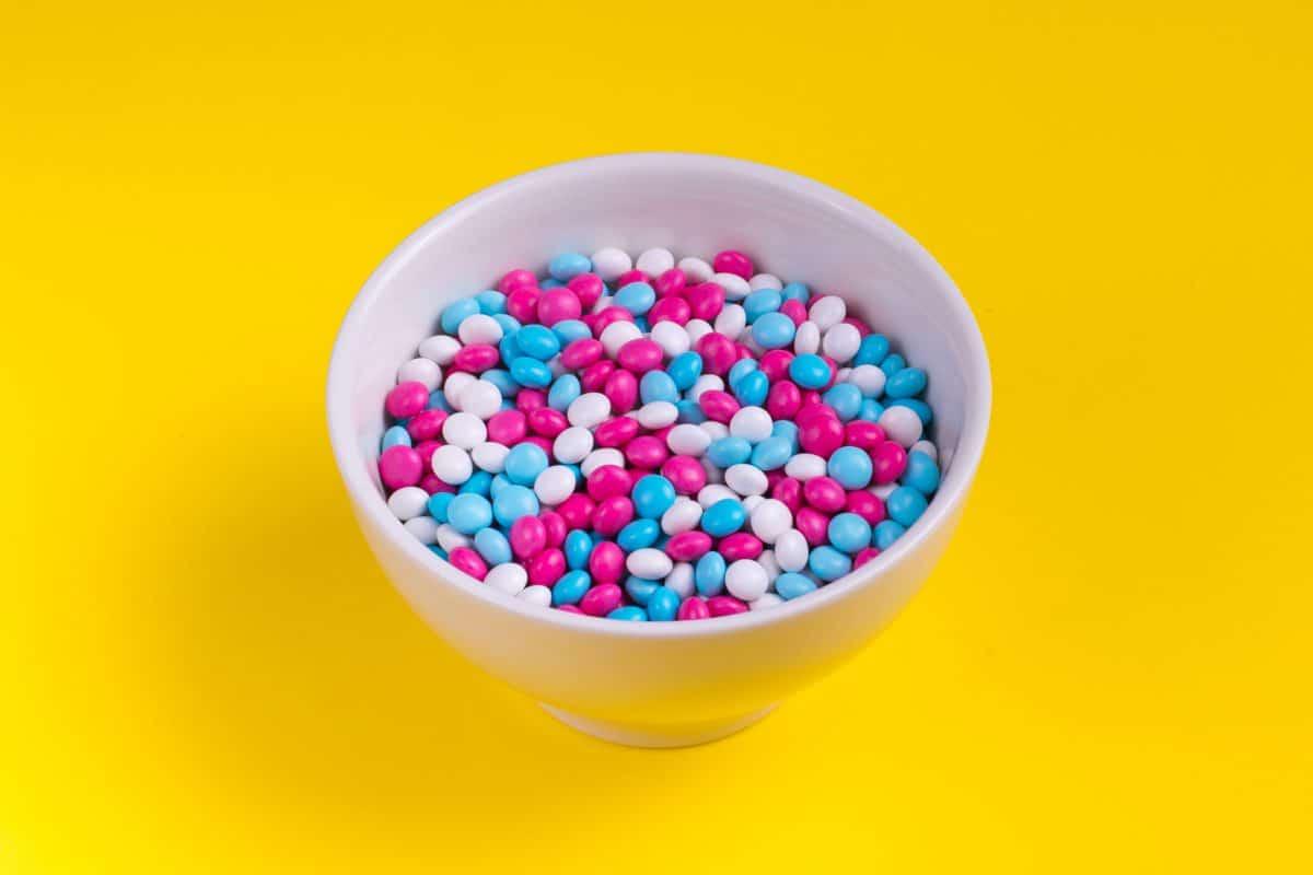 O objetivo da Omens é ajudar a entender a diferença entre viagra e cialis. A imagem mostra uma tigela cheia de pílulas de cor azul, branca e rosa num fundo amarelo.