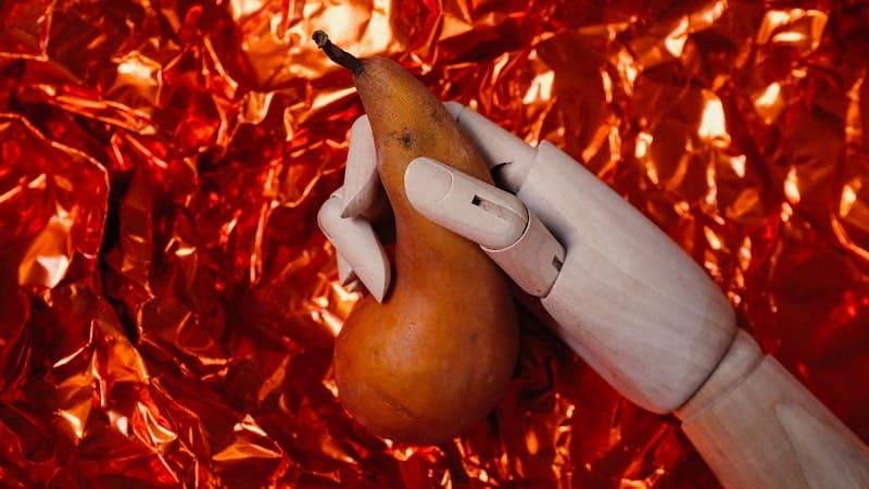 Uma mão segura uma fruta madura em fundo avermelhado – vamos falar sobre o que é libido e como resolver o seu problema com a Omens
