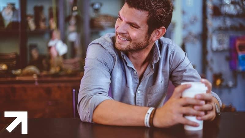 homem sentado à mesa contente com uma possível calvície controlada pela finasterida